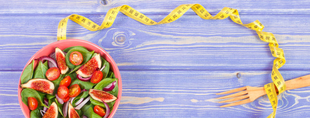 Fruit and vegetable salad, fork with tape measure, slimming and nutrition concept, copy space for text