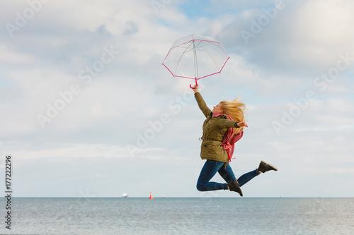 Juliste Woman jumping with transparent umbrella on beach