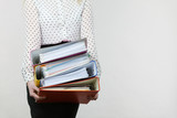 Woman holding heavy colorful binders with documents - 177223092