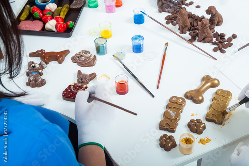 Wall mural Close-up of a woman a confectioner in blue uniform and white gloves paints New Year's candies of milk chocolate with edible paint, on the table lie other Christmas candy-dogs, the top view