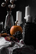 Autumn decor of a table with a pumpkin, white candles, fruits and Viennese wafers