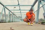 Urban jogger tying running shoes on the asphalt.