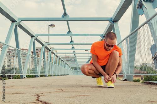 Plakat Urban jogger tying running shoes on the asphalt.