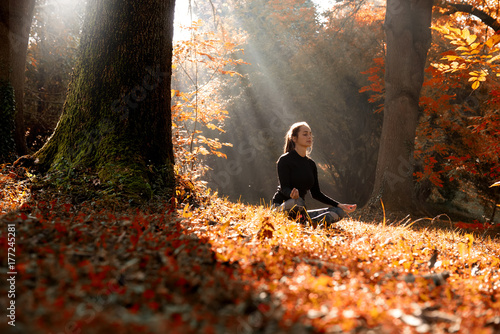 Plakat A young woman make yoga position at sunrise. in the autumn forest.