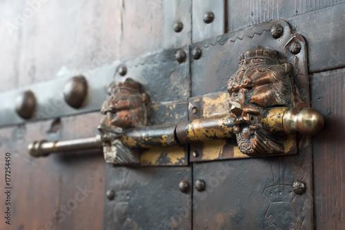 Lion head chinese door locker on a brown wooden door, China Poster