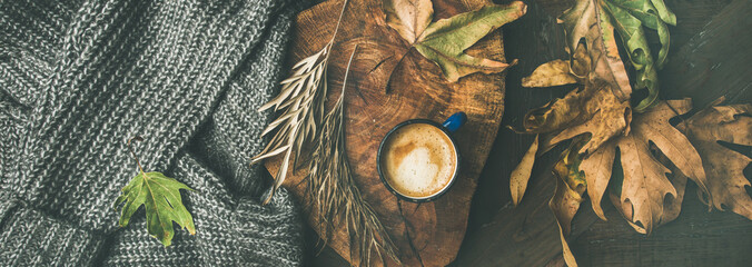 Autumn or Fall morning coffee concept. Flat-lay of knitted woolen grey sweater, wooden tray, mug of coffee and yellow fallen leaves over dark rustic wooden table background, top view, wide composition © sonyakamoz