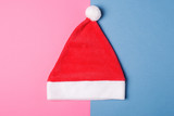 Santa Claus red hat on blue and pink paper background , minimal style.