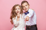 Boy and girl standing in studio on pink background