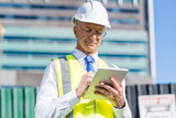 Construction manager controlling building site and tablet device in his hands - 177288022