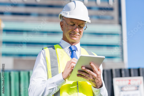 Fridge magnet Construction manager controlling building site and tablet device in his hands