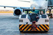 The tow truck drive up at the passenger aircraft parked to a jet bridge