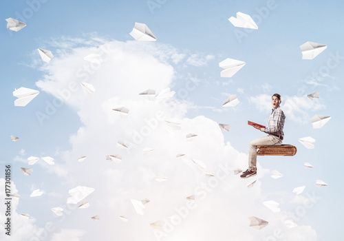 Handsome man student reading book and paper planes flying around