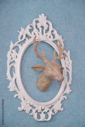 Poster The golden head of a deer in a white openwork frame.