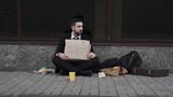 Unemployed sad businessman sitting on pavement with cardboard. - 177330600
