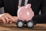Businessperson Pushing Piggy Bank On Wheels - 177348260