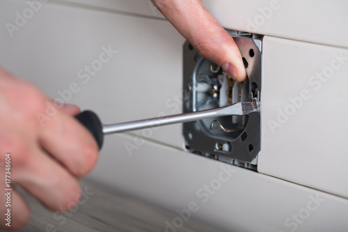 Person's Hand Repairing Electrical Socket Poster