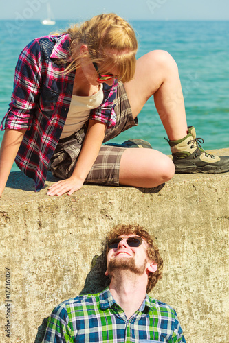 hiking couple relaxing on sea coast Poster