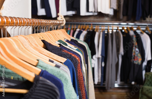 Different assortment of colorful clothing in  boutique Poster