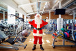 Santa Claus in the gym doing the exercises.