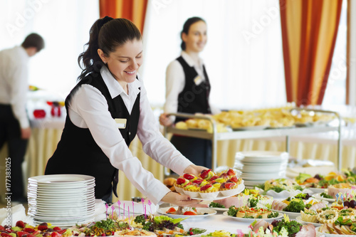 Restaurant waitress serving table with food - 177383025