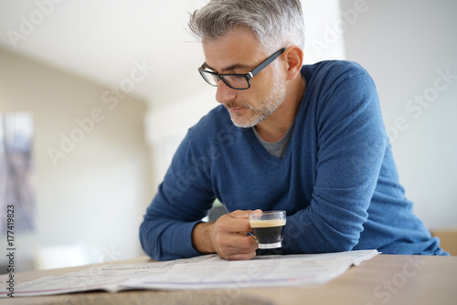 Wall mural Middle-aged man at home drinking coffee and reading newspaper