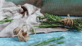A bunch of fresh rosemary on linen cloth, Rustic greenery on blue wooden background. - 177434290