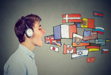 Fototapety Young man in headphones learning different languages