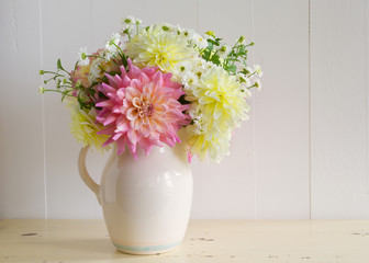 Dahlia and matricaria in an old fashioned ceramic pitcher.