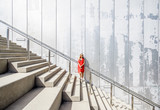 Business woman in red dress on the big stairway on the grey wall background - 177454893