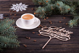 The cup of coffee stands on a wooden table. Congratulation Merry Christmas.