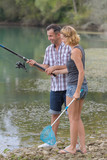 lovely young couple fishing together by a lake - 177478403