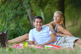 young beautiful couple lying on the lawn in the park - 177480407