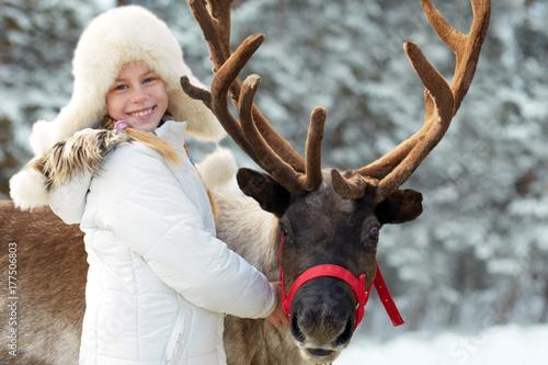 Winter playtime.Happy little girl hugging her reindeer.