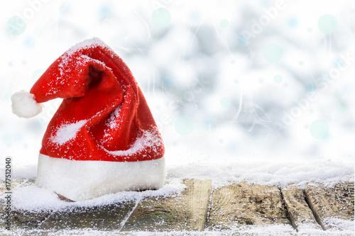 Weihnachtsmütze auf verschneitem Holzboden vor Winterhimmel mit Bokeh