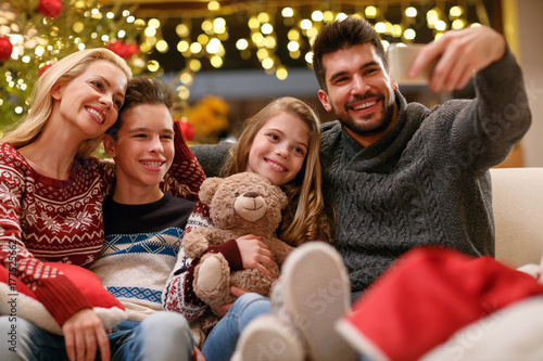 Family on Christmas holiday making selfie together