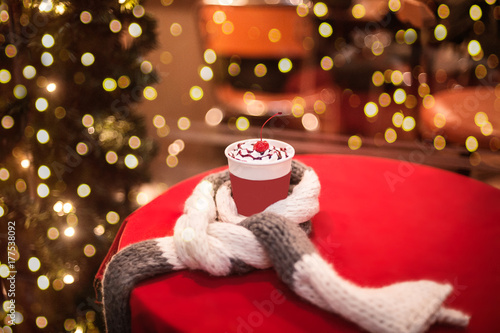 Coffee to go with wripped cream and cherry on a table covered with wool scarf, bokeh lights on background