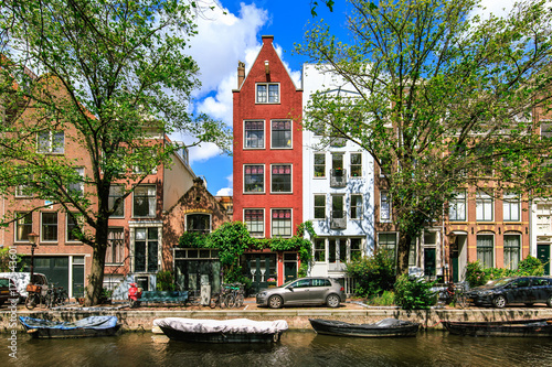 Traditional dutch houses and boats on canal in Amsterdam Poster