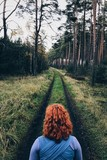 Red head woman on the forest path. - 177570894