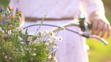 Basket with flowers close-up. Woman standing near her bicycle at sunset. - 177582246