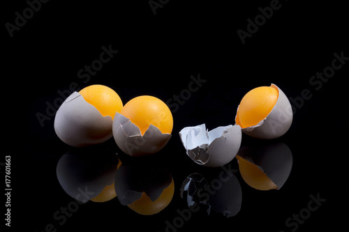 Fotobehang Abstractie Still life with eggshell and orange balls on a black background