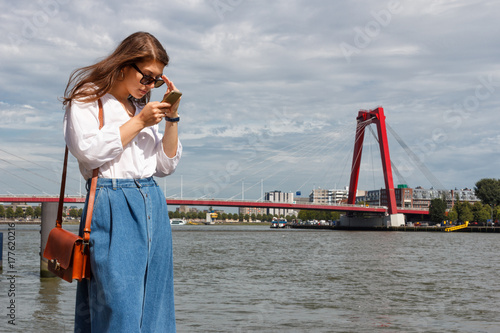 Foto op Plexiglas Rotterdam Stylish young woman with mobile phone on background of the city of Rotterdam.