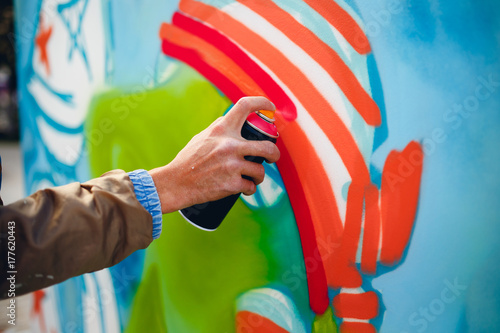 Artist graffiti with a balloon paint in his hands draws on the wall - 177620443