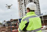 Fototapety Drone operated by construction worker on building site