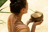 Woman with coconut drink under palm leaf
