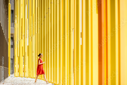 Woman in red dress walking on the modern yellow building wall background Poster