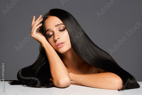 Foto Spatwand Kapsalon Portrait of attractive woman with straight hair closed eyes on gray background