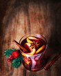 Christmas Mulled Wine for winter on wooden background. Hot wine with spices and Christmas Decorations. Traditional drink on winter holiday in rustic style.