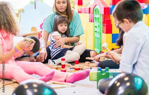 Gruppe von Kindern im Kindergarten mit Erzieherin beim Spielen