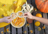 Autumn pumpkin composition on the wooden table. Organic food composition: rape oranges, pears, physalis and white wine. French wine on the countryside weekend. Happy time outdoors. White wine on table