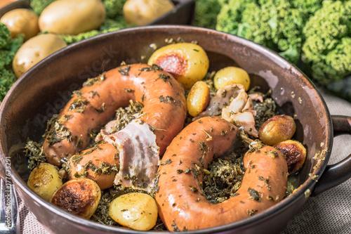 Leinwanddruck Bild Grünkohl mit Bregenwurst und Röstkartoffeln